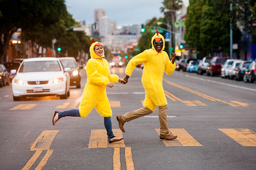 Couple in chicken costumes crossing city street